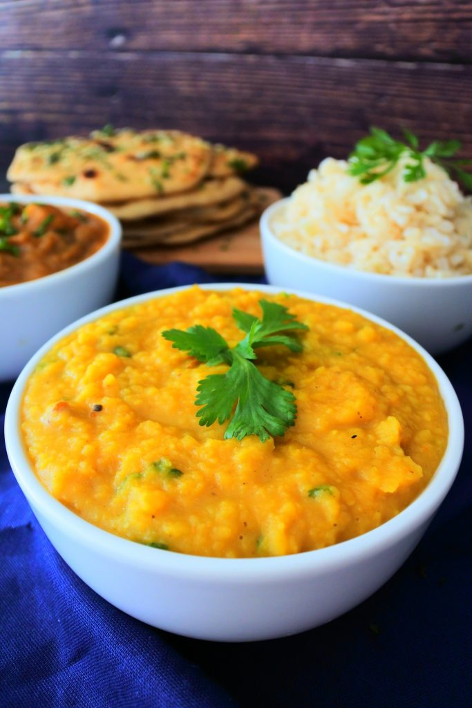 A vertically angled close up image of a bowl of dhal, a bowl of curry, a bowl of rice and a stack of garlic naan on a blue cloth with a wood-grained background