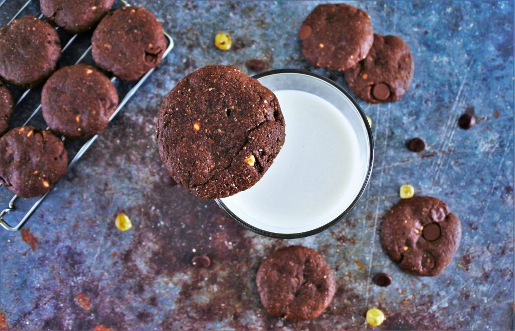 An overhead image of a glass of milk with a Double Chocolate Hazelnut Cookie balanced on the rim of the glass surrounded by other cookies