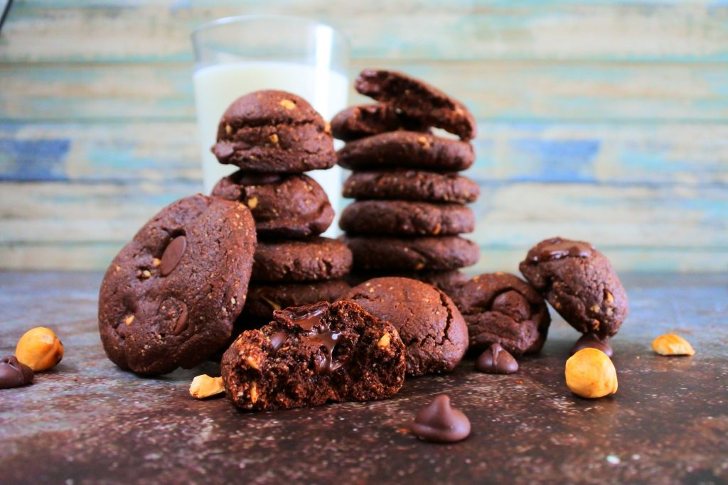 A head on image of two stacks of Double Chocolate Hazelnut cookies with other cookies propped up around the stacks surrounded by chocolate chips and hazelnuts on the tabletop and with a glass of milk in the background