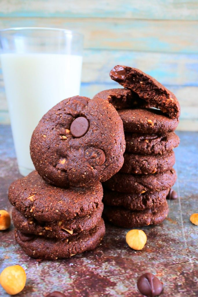 A head on image of two stacks of Double Chocolate Hazelnut cookies surrounded by chocolate chips and hazelnuts on the tabletop and with a glass of milk in the background
