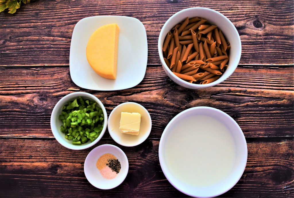 An overhead image of plates and dishes containing ingredients such as: whole grain pasta, milk, smoked Gouda, a pat of butter, salt, black pepper, garlic powder, and diced green bell peppers