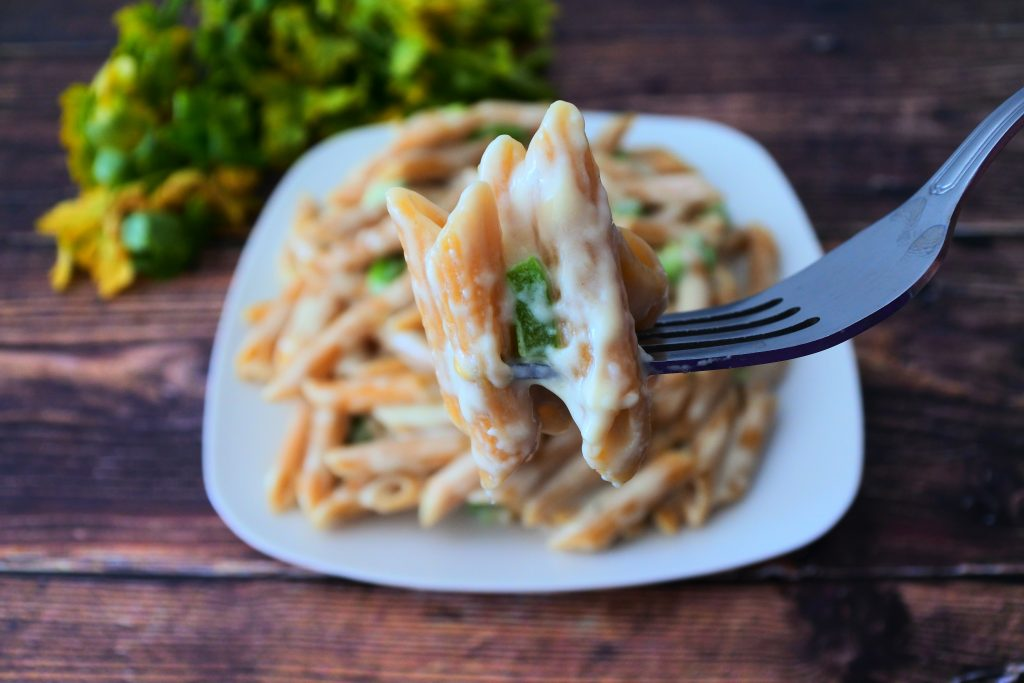 A close up image of a forkful of smoked Gouda mac and cheese with a plate of mac and cheese and a bundle of fresh herbs in the background