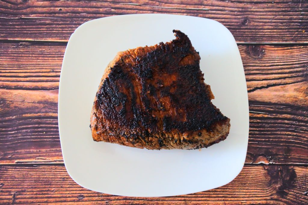 An overhead image of a charred and cooked slab of steak on a plate