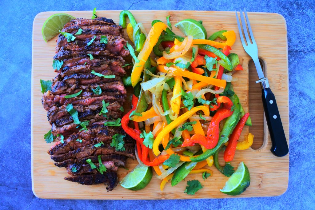 An overhead image of a bamboo board with cooked and sliced steak on the left and an assortment of multi-colored bell peppers and onions on the right with a fork on the edge of the board