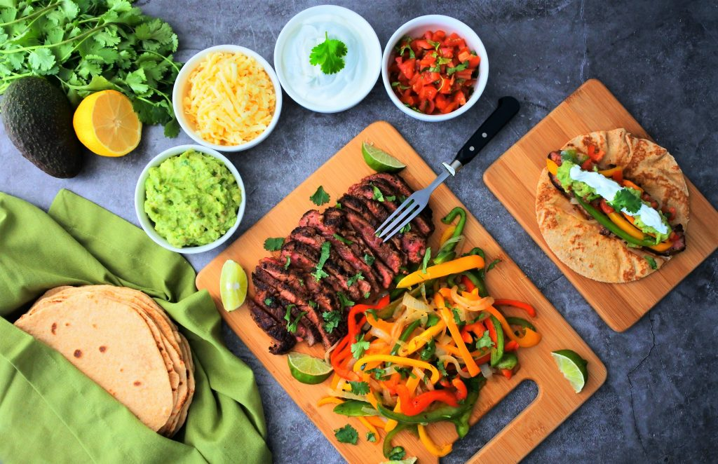 An overhead image of a bamboo board of sliced steak and bell peppers with onions surrounded by bowls of cheese, sour cream, diced tomatoes and guacamole, as well as a prepared fajita on a smaller board, with a stack of flour tortillas in the bottom left and a lemon, avocado and fresh herbs in the top left