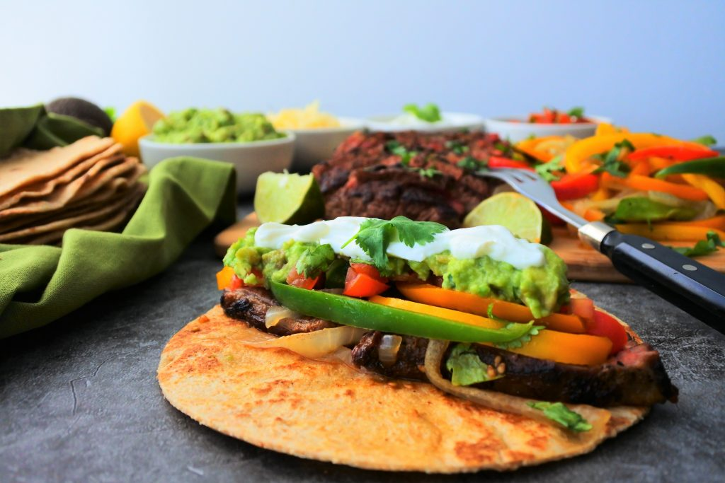 A head on image of a steak fajita on a flour tortilla topped with sour cream, guacamole, and tomatoes