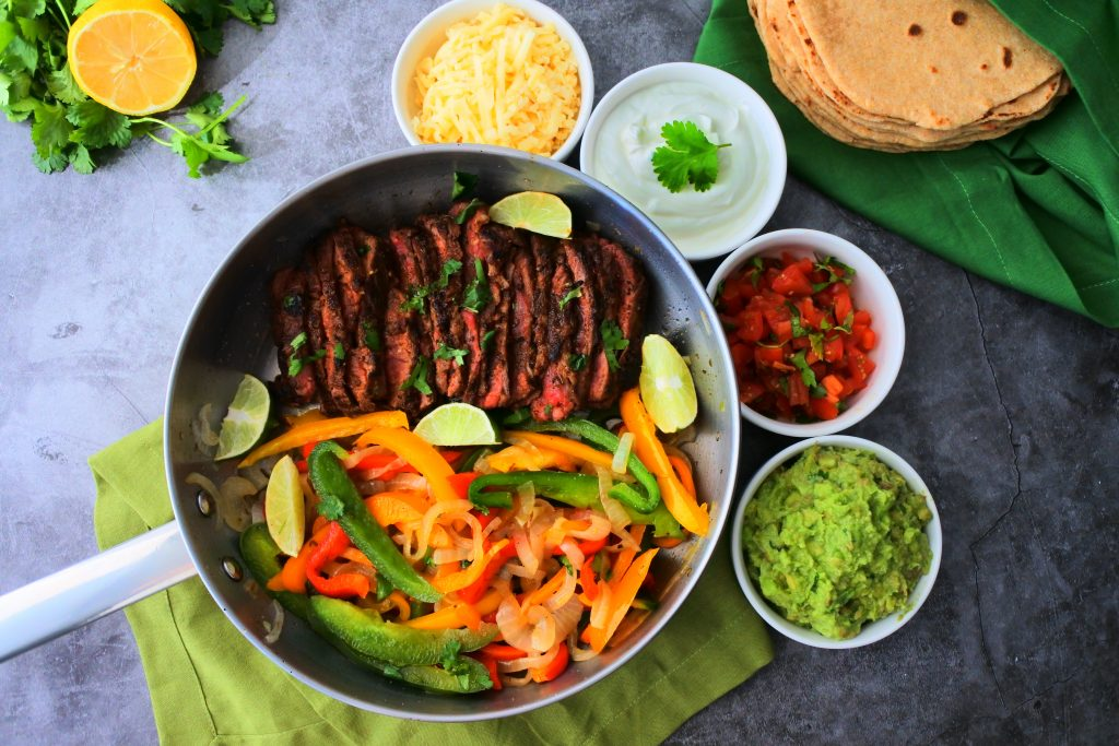 An overhead image of a pan of sliced steak and bell peppers with onions surrounded by bowls of cheese, sour cream, diced tomatoes and guacamole with a stack of flour tortillas in the top right and a lemon and fresh herbs in the top left