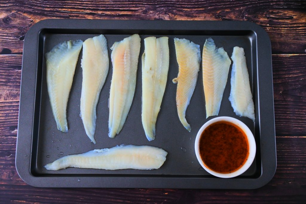 An overhead image of a tray of white fish fillets with a bowl of olive oil based lemon pepper seasoning in the bottom right hand corner of the tray.