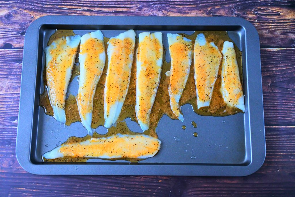 An overhead image of a tray of fish fillets coated in a lemon pepper seasoned olive oil.