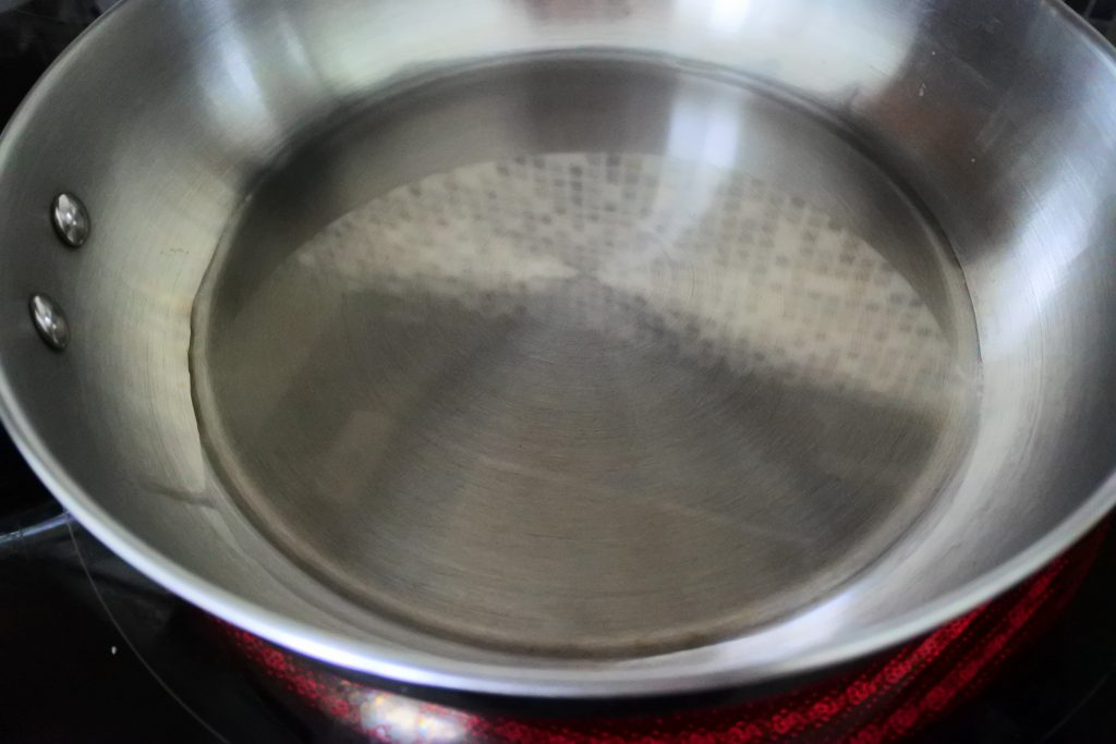 An angled overhead image of a pan with olive oil on an electric glass top burner.