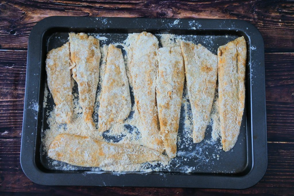 An overhead image of a tray of floured fish fillets.