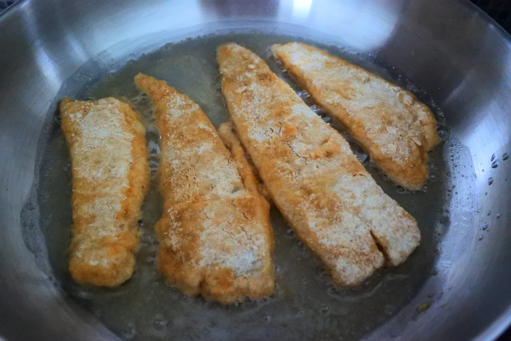 An angled image of four lightly floured fish fillets frying in an olive oil-coated pan.