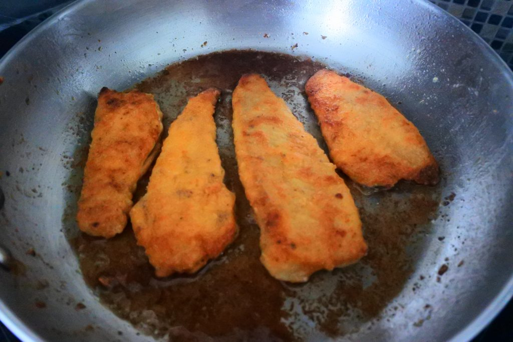 An angled image of four golden brown fish fillets frying in a pan.