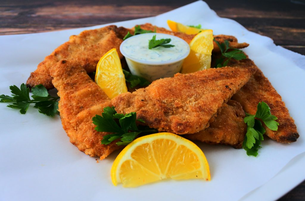 An angled, head on image of golden fried fish fillets on parchment paper served with tartar sauce in the center and garnished with lemon wedges and fresh parsley.