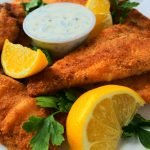 A vertical angled image of golden fried fish fillets with tartar sauce, garnished with lemon wedges and parsley.