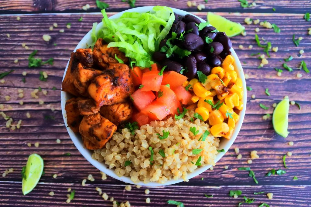 An overhead image of a quinoa power bowl containing fluffy quinoa, chipotle chicken, shredded lettuce, black beans, roasted corn and fresh tomatoes all garnished with finely shredded cilantro and lime wedges