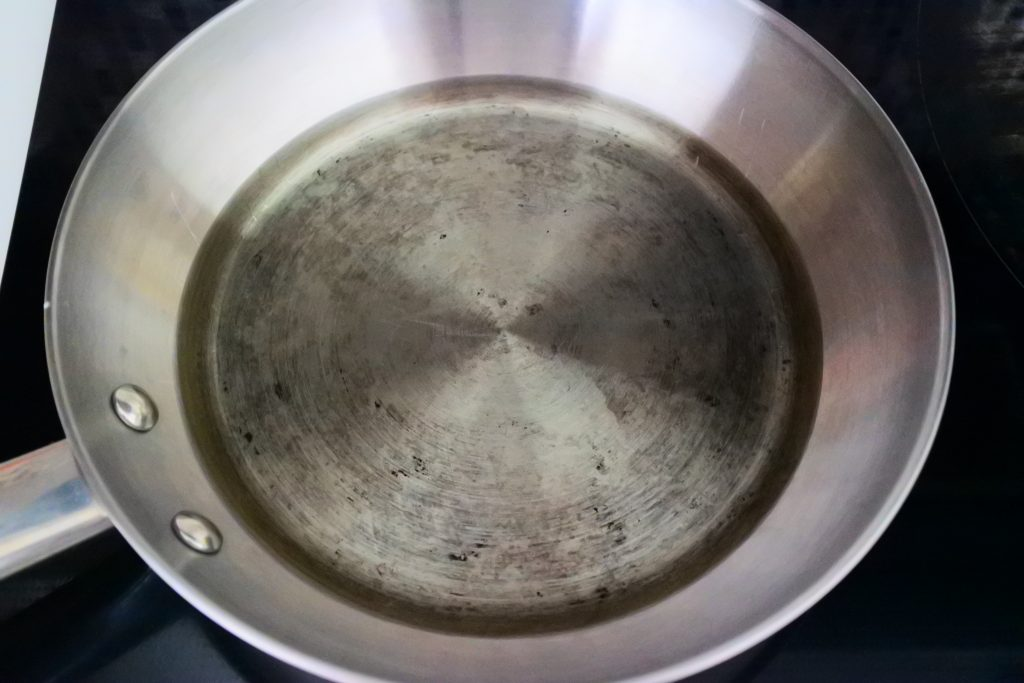 An angled overhead image of a frying pan with a half inch of oil.