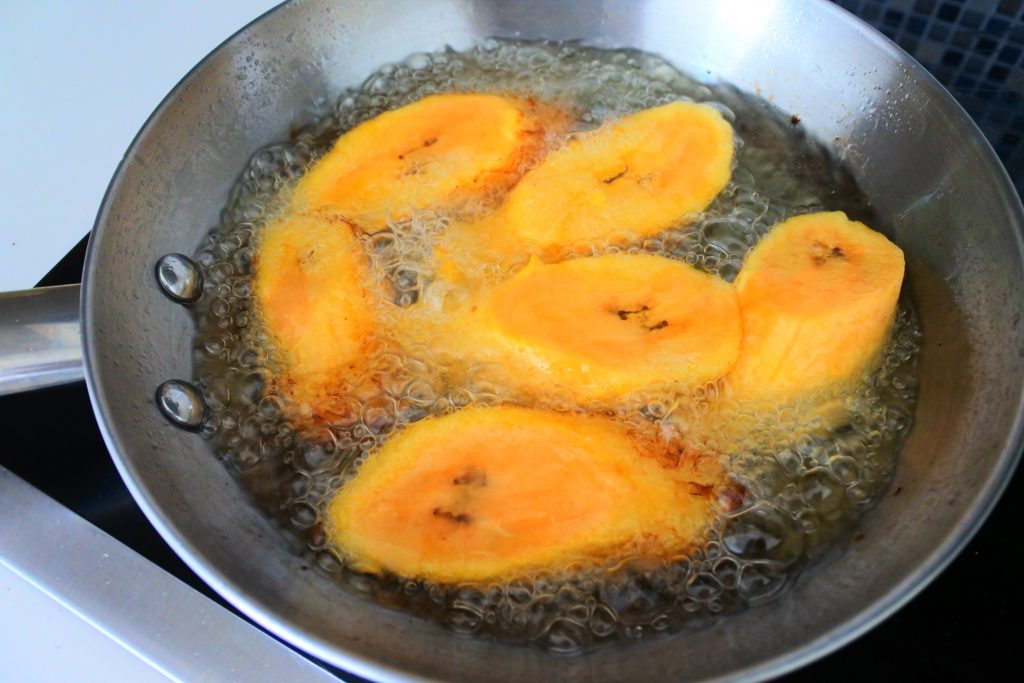 An angled overhead image of slices of plantains in a frying pan being fried in oil.