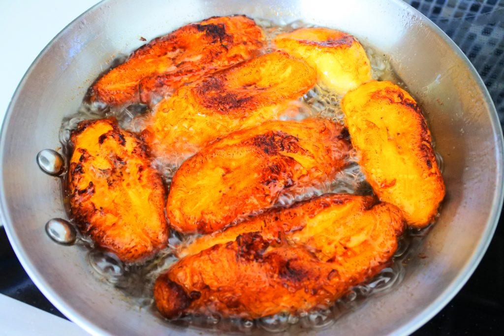 An overhead image of semi-fried slices of plantain in a pan of hot oil
