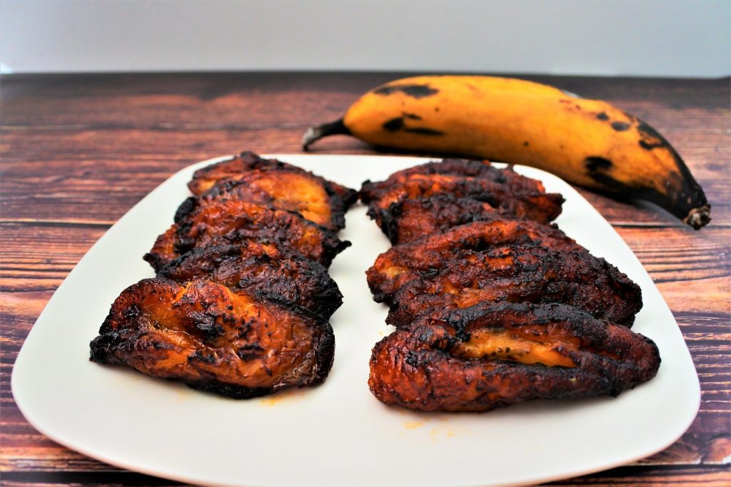 A close up image of slices of fried plantains on a plate with a whole plantain in the background