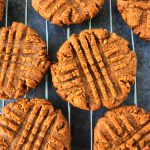 An overhead image of peanut butter cookies on a wire cooling rack