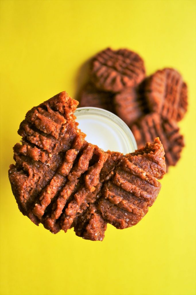 An overhead image of a peanut butter cookie with a bite taken out of it balancing on the neck of a bottle of milk with a pile of peanut butter cookies below on a yellow surface