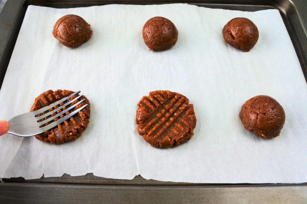 An angled image of a parchment lined tray with portions of peanut butter cookie dough on it. One round of dough has been pressed with a cross hatch mark while another is being pressed down with the flat tines of a fork