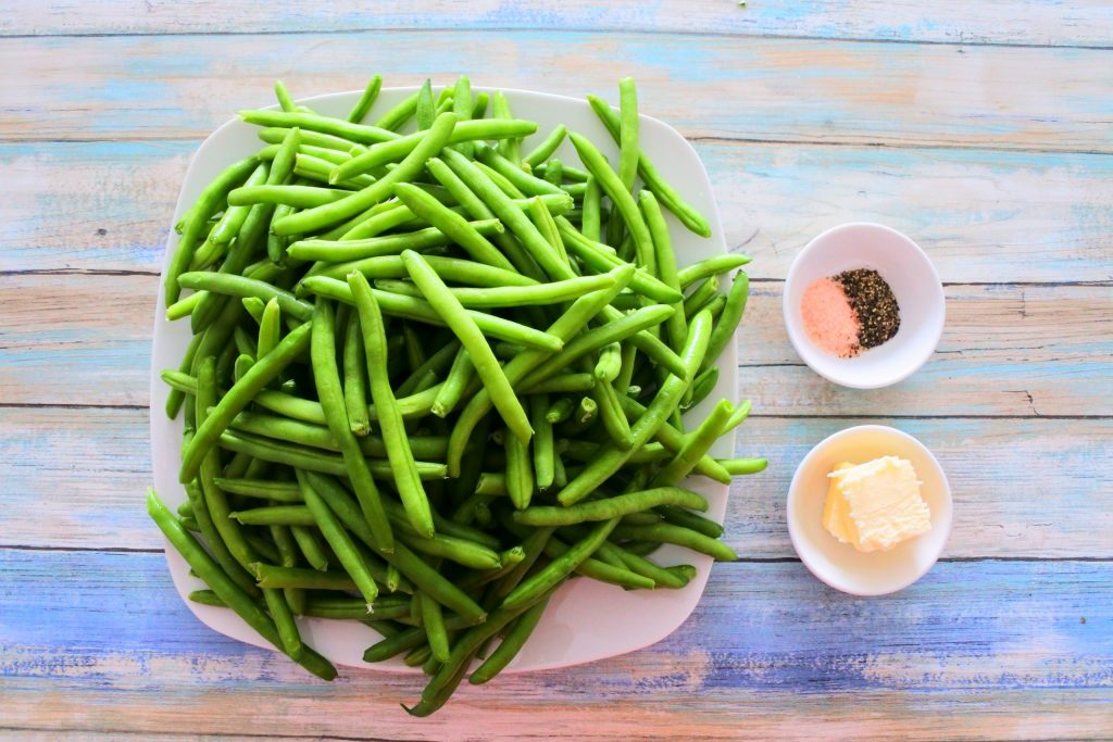 An overhead image of a plate of green beans next to small dishes of butter and salt and pepper.