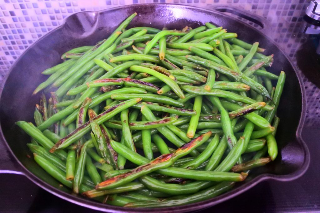 An angled image of a skillet of blistered green beans.