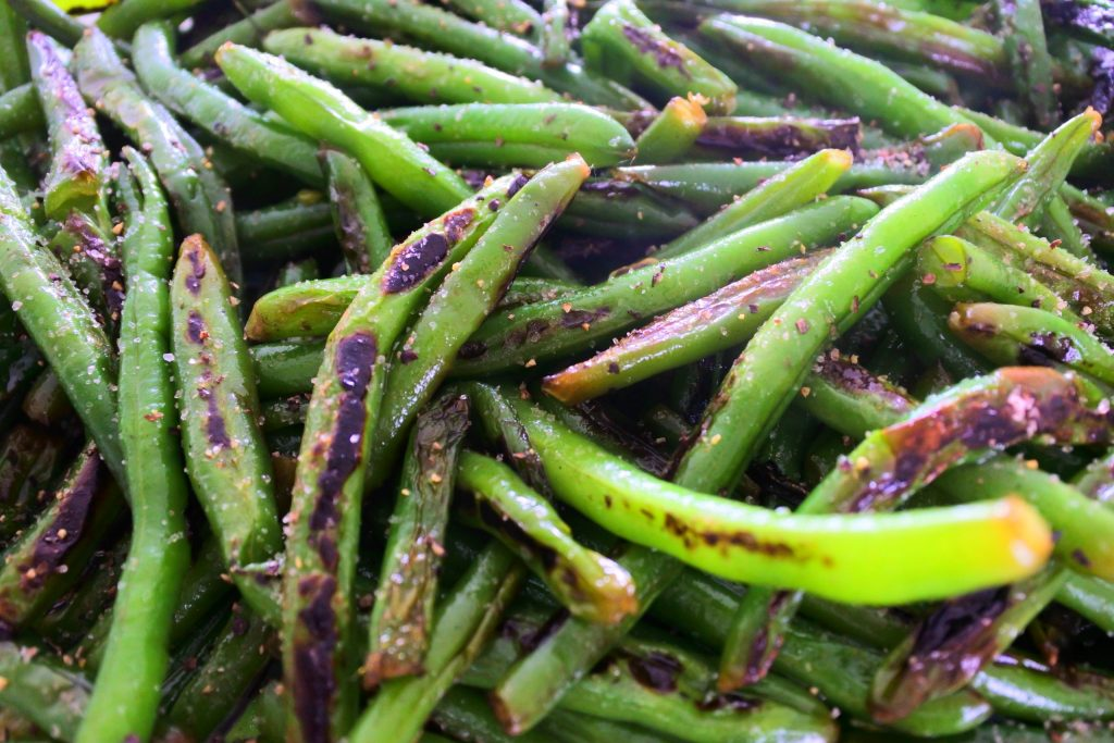 A close up image of blistered green beans seasoned with salt and pepper