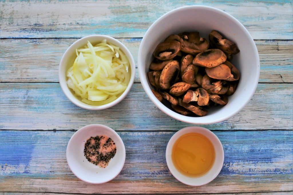 An overhead image of bowls containing sliced onions, mushrooms, oil and salt and pepper
