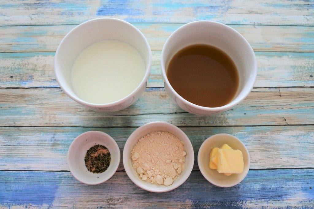 An overhead image of ingredients for a simple roux sauce including milk, broth, butter, whole wheat pastry flour and salt and pepper