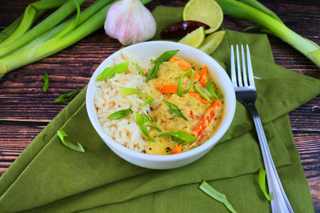 An angled image of a bowl of coconut rice with Thai green curry and chicken meatballs topped with sliced chives
