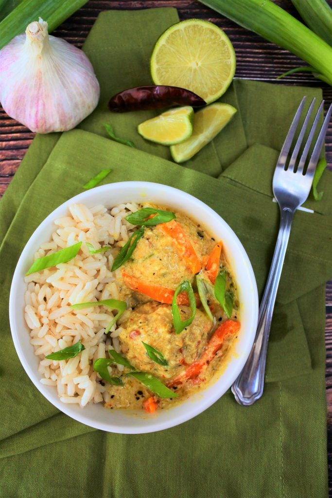 An overhead image of a bowl of coconut rice with Thai green curry and chicken meatballs topped with sliced chives on a green linen napkin surrounded by herbs and spices and a silver fork