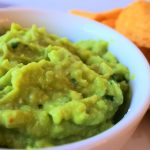 An angled head on image of a bowl of guacamole with yellow corn tortilla chips in the background
