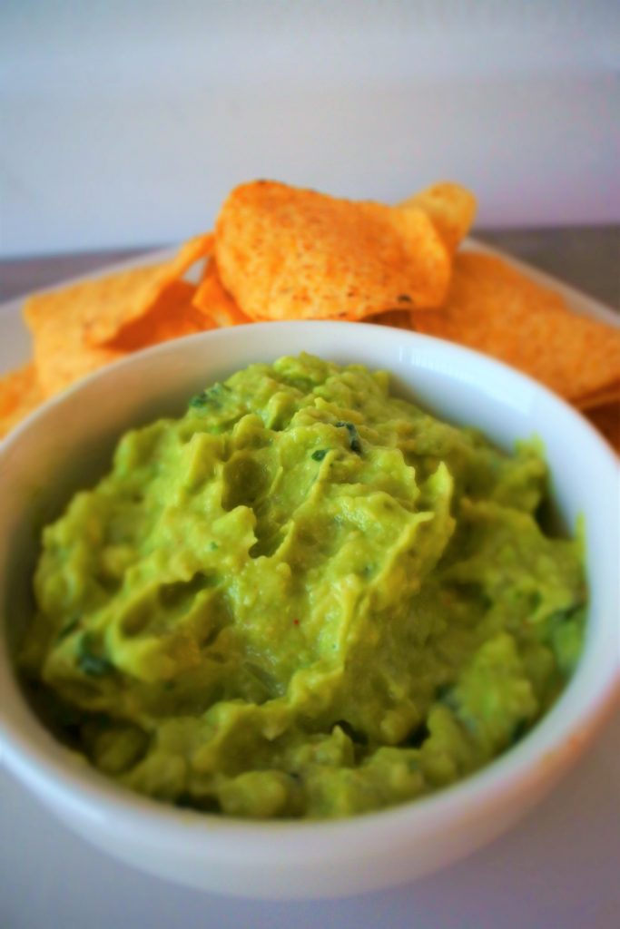 A tilted angle image of a bowl of guacamole with yellow corn tortilla chips in the background