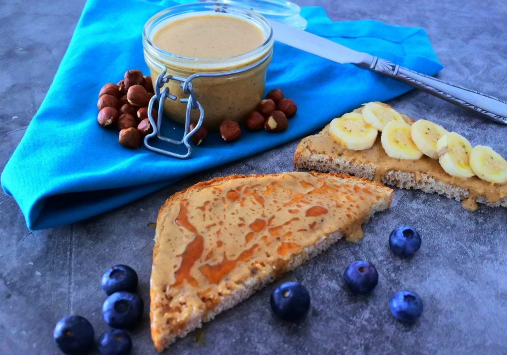 Angled image of a jar of homemade hazelnut butter on a blue napkin with a slice of toast with honey drizzled over it and fruit.