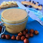 A close up image of a jar of homemade hazelnut butter on a blue cloth napkin surrounded by hazelnuts with a knife leaning against the jar and pieces of toast covered with hazelnut butter and fruit in the background