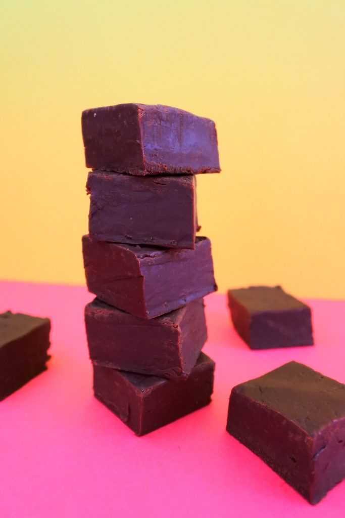 A head on image of a stack of homemade chocolate fudge pieces on a pink surface with a yellow background