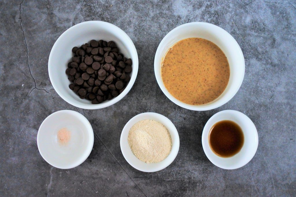 An overhead image of bowls of ingredients for a homemade chocolate hazelnut spread including dark chocolate chips, homemade hazelnut butter, vanilla extract, finely ground raw cane sugar, and a pinch of salt