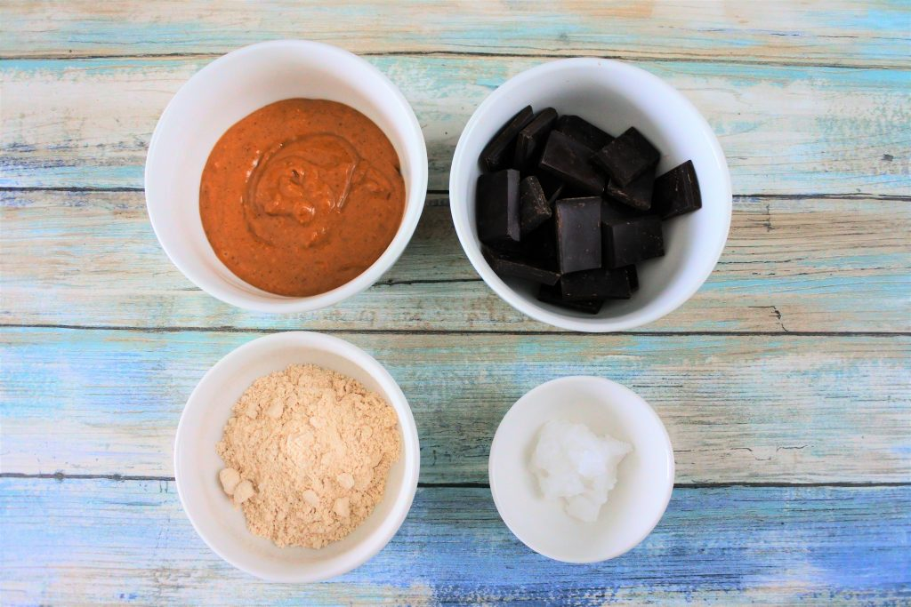 An overhead image of four bowls containing natural peanut butter, dark chocolate squares, finely ground raw cane sugar and coconut oil