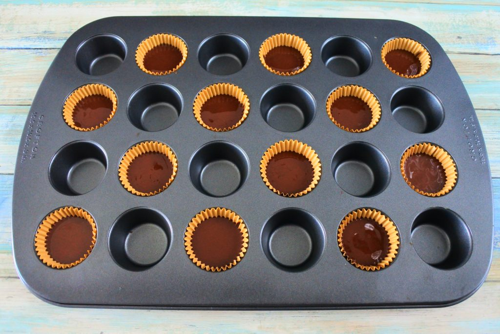 An angled overhead image of a mini muffin tin with paper liners filled with chocolate