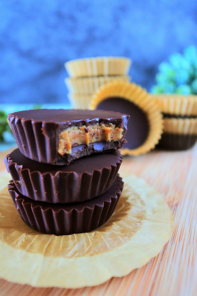 A head on close up image of a stack of three peanut butter cups with a bite taken out of the top one with paper lined peanut butter cups in the background