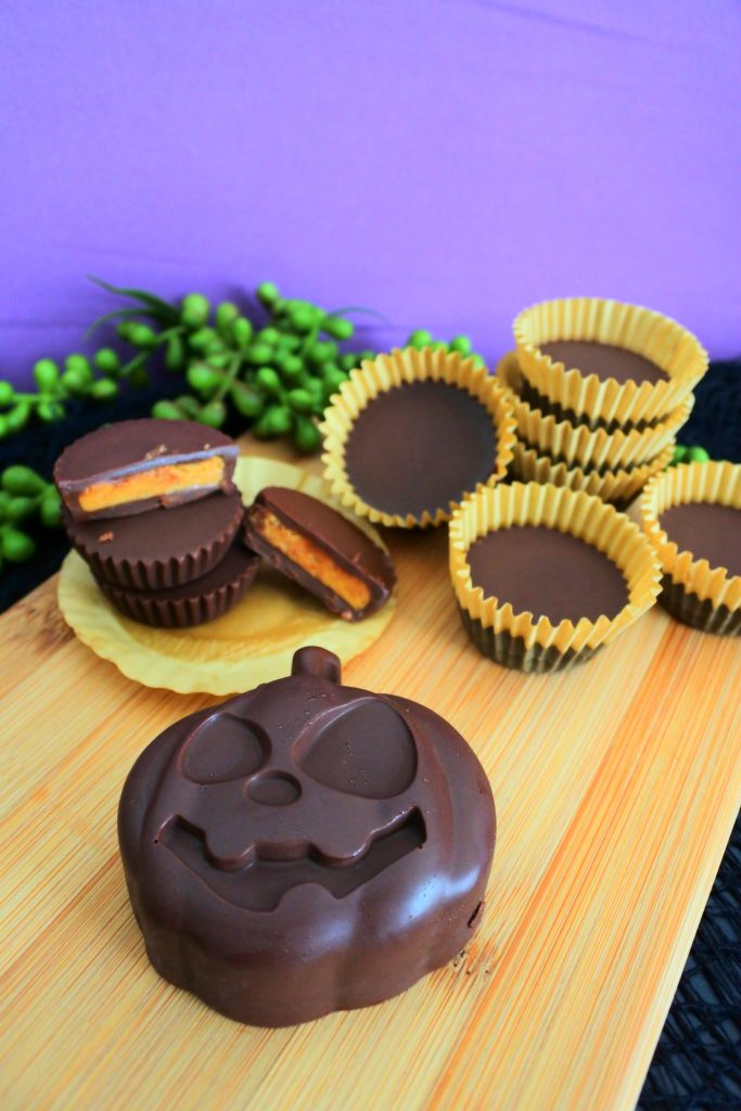 A close up head on image of a pumpkin-shaped Halloween peanut butter cup with regular peanut butter cups in the background