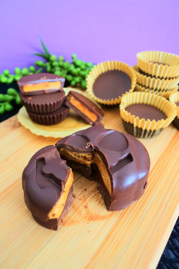 A close up head on image of a split open Halloween pumpkin-shaped peanut butter cup with regular peanut butter cups in the background
