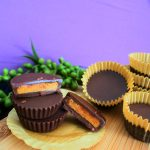 A head on close up image of homemade peanut butter cups on a wooden plank with one cut in half to show the peanut butter interior against a purple background