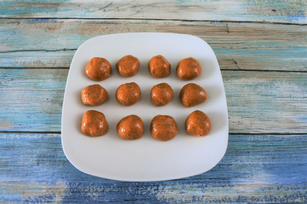 An angled overhead image of plate of twelve peanut butter balls