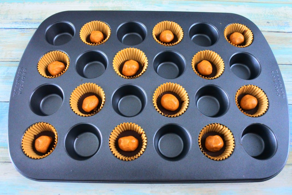 An angled overhead image of a mini muffin tin with paper liners filled with peanut butter balls on a chocolate base