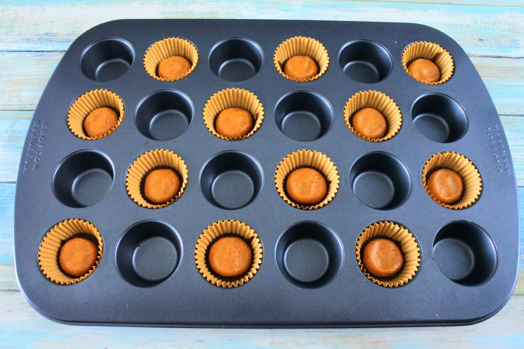 An angled overhead image of a mini muffin tin with paper liners filled with flattened peanut butter balls on a chocolate base