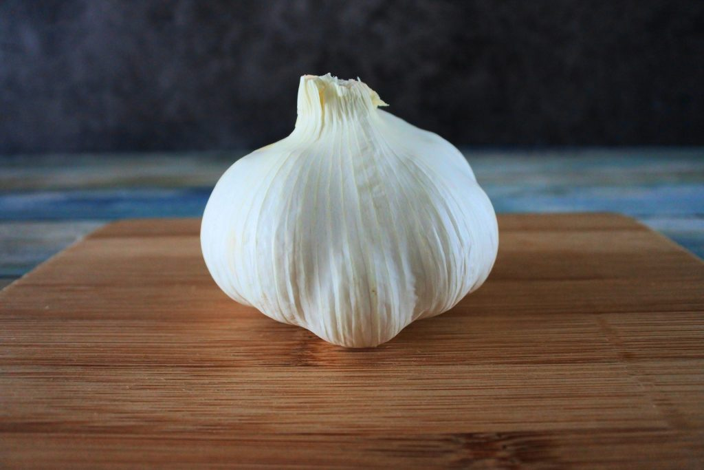 A head on image of a head of garlic on a wooden board
